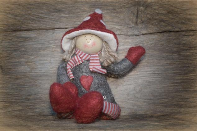 Une poupée en chiffon en rouge et gris.